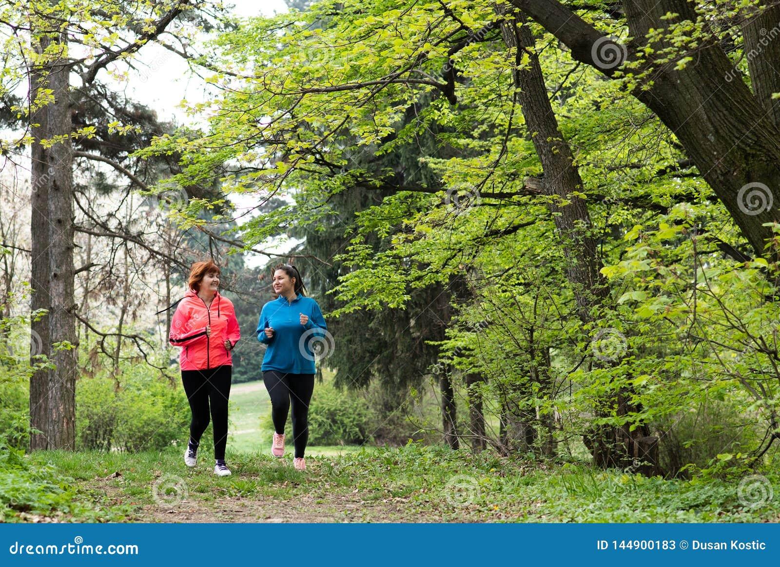 Matka i c?rka jest ubranym sportswear i bieg w lesie