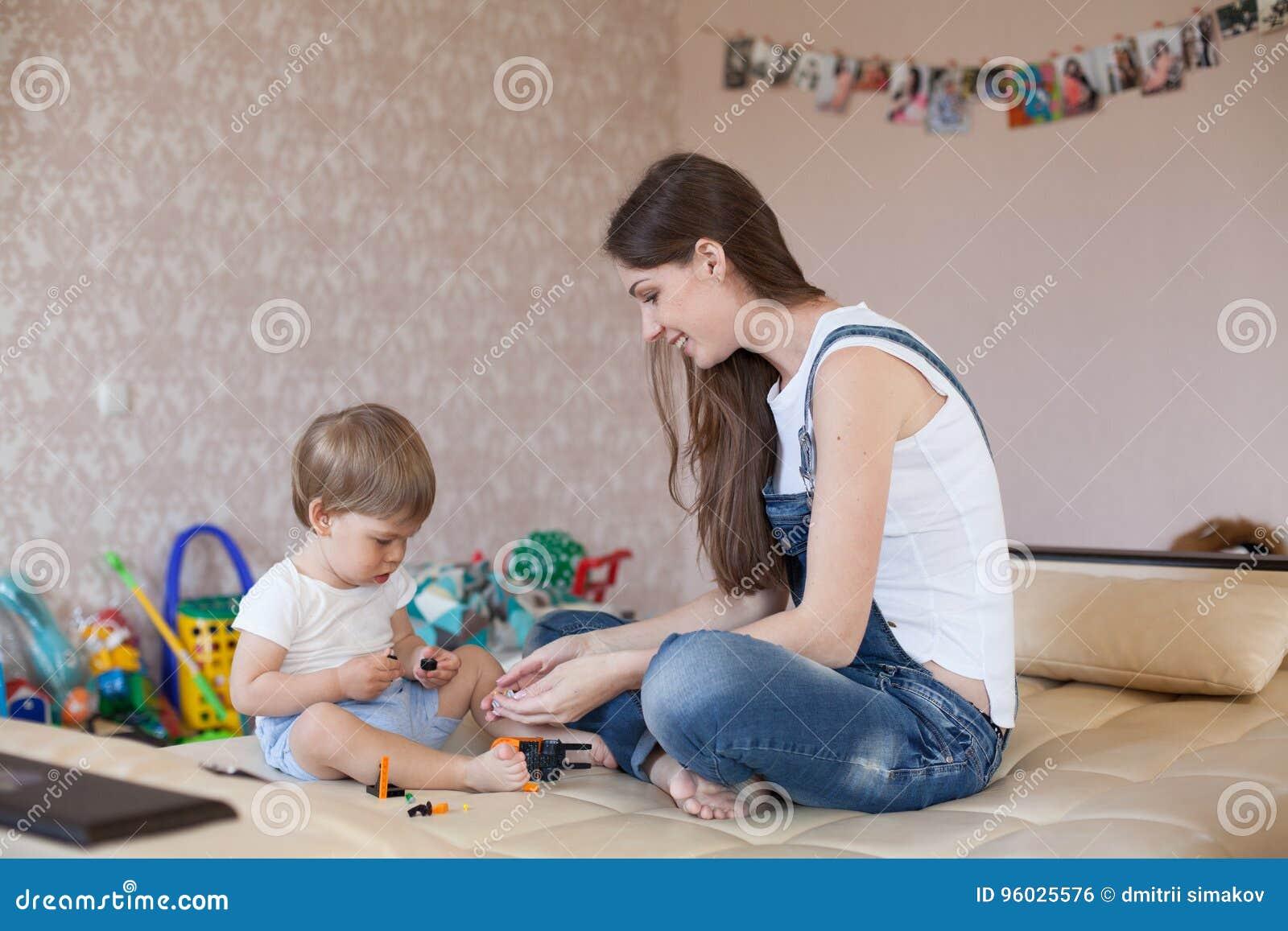 Matka i chłopiec bawić się z zabawkami w pepinierze
