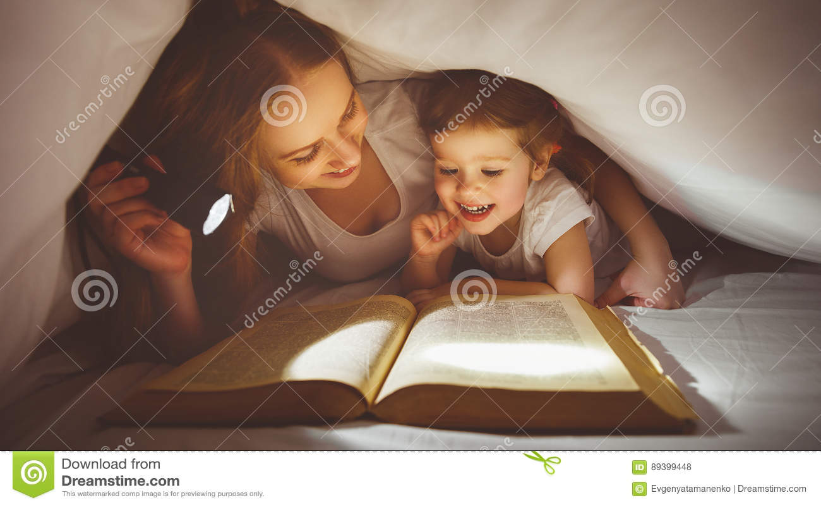 Matka i dziecko czytamy książkę pod koc z latarką
