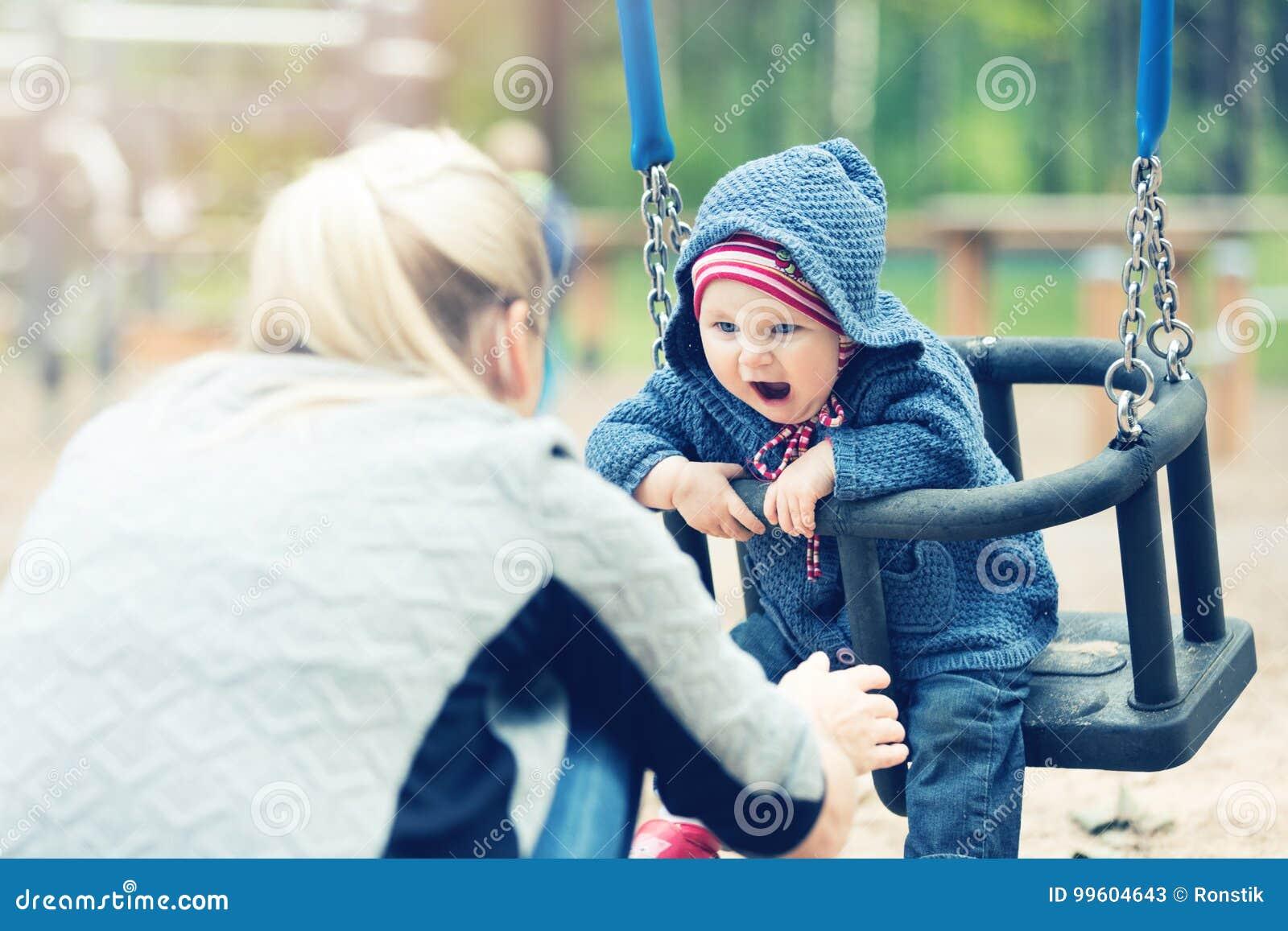 Matka i dziecko ma zabawę w huśtawce przy boiskiem
