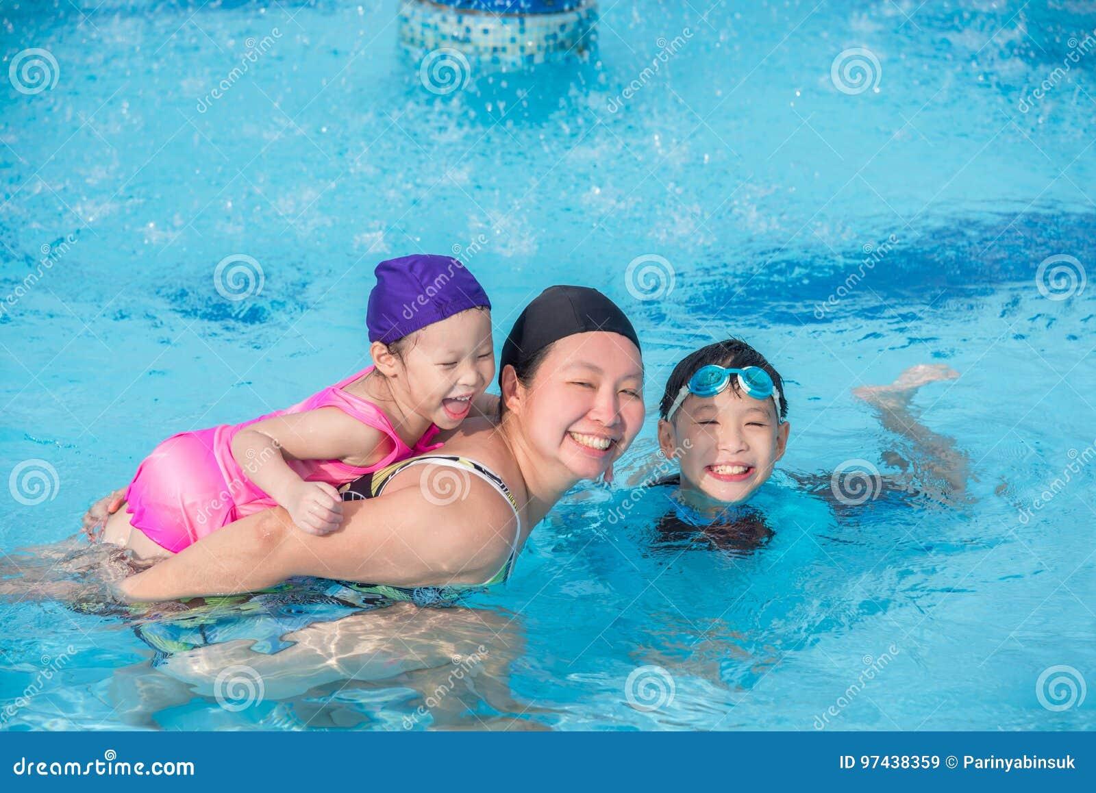 Matka i jej dzieci szczęśliwi w pływackim basenie
