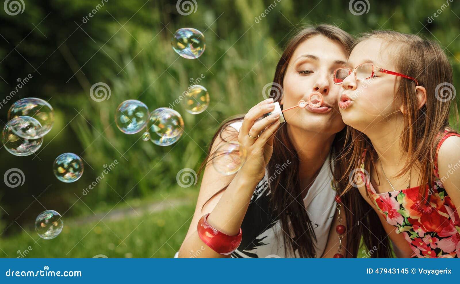 Matka i mała dziewczynka dmucha mydlanych bąble w parku