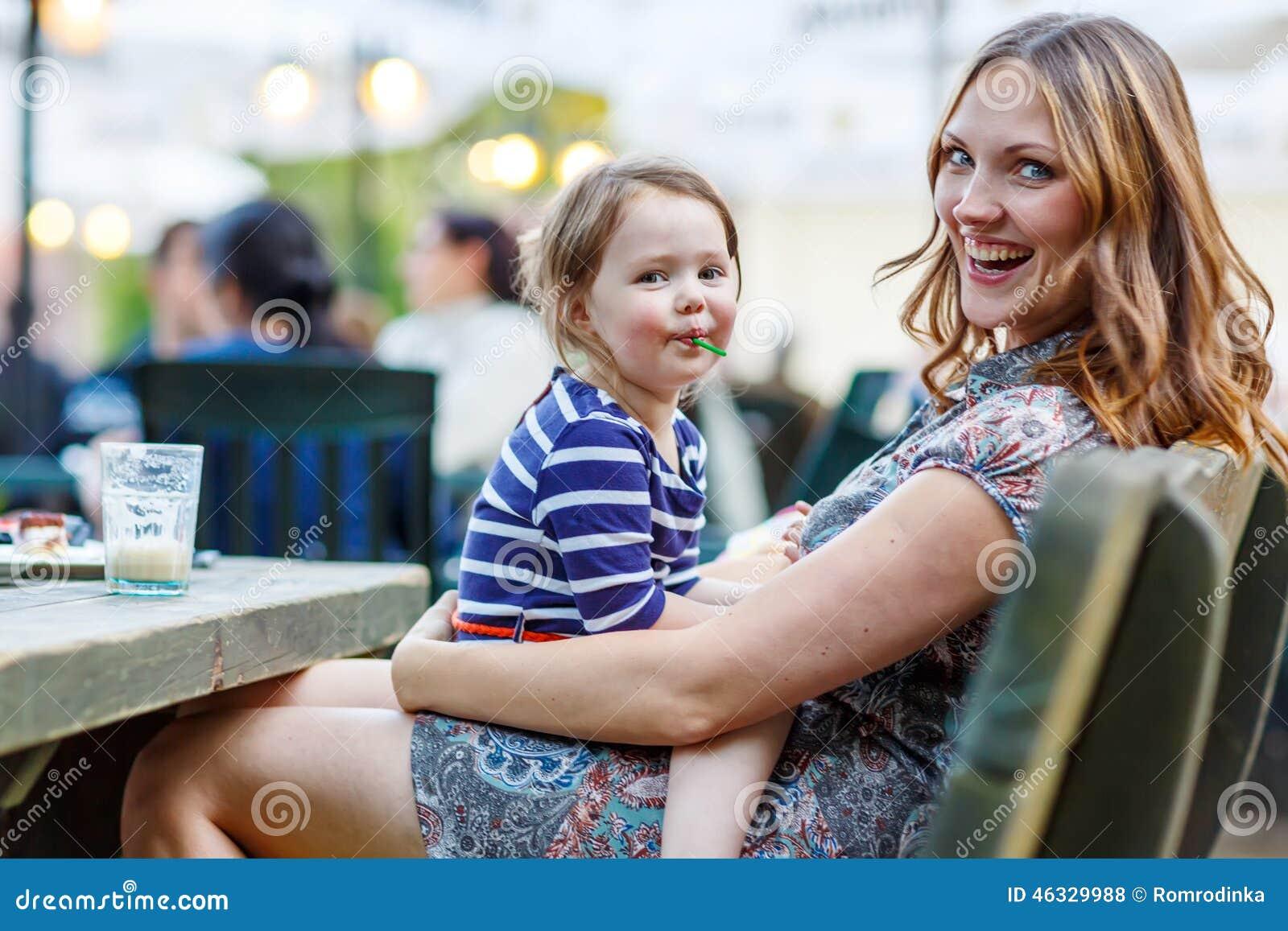 Matka i mała urocza dzieciak dziewczyna pije kawę w plenerowym c
