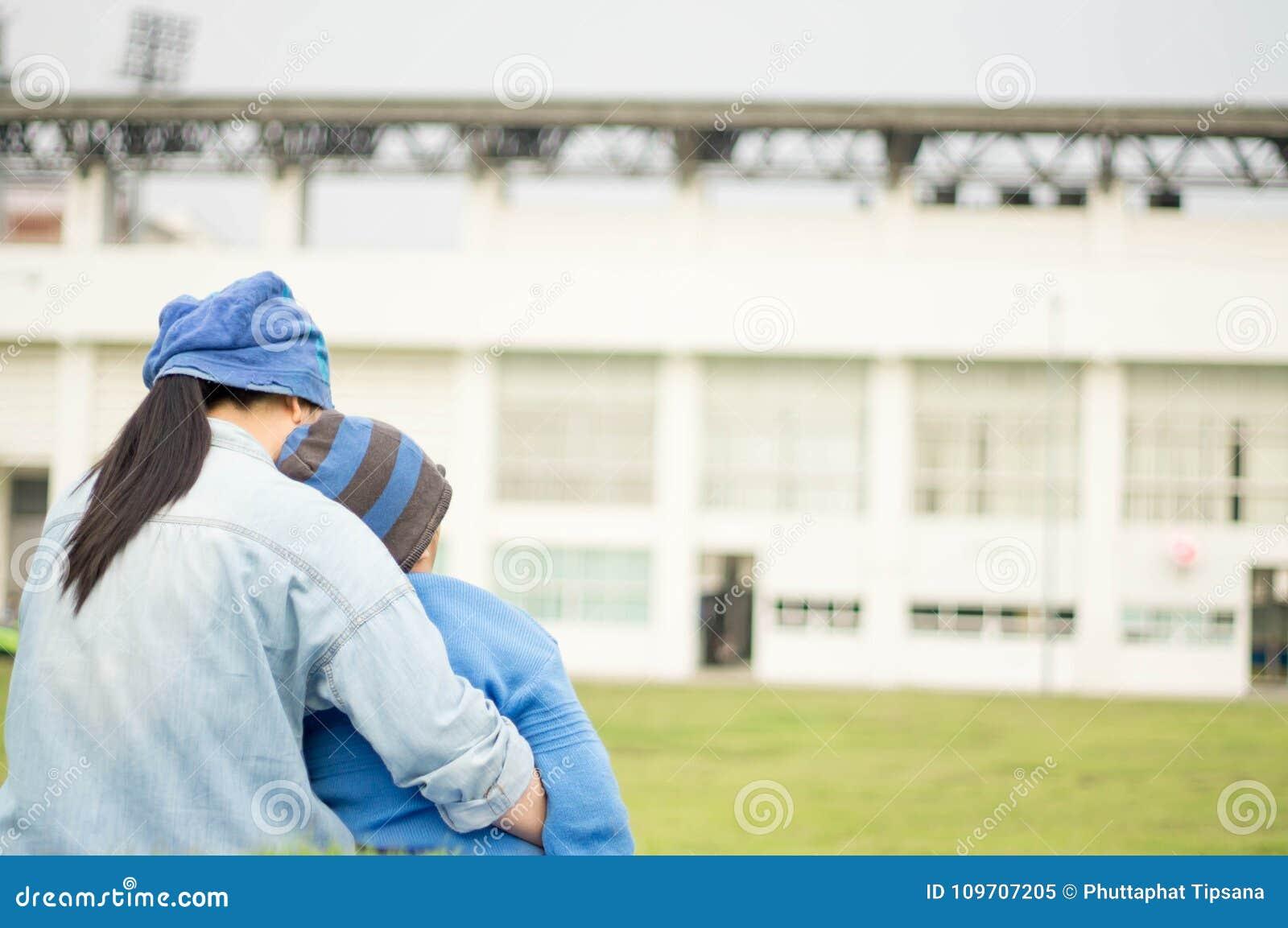 Matka, syn w parku, boisko piłkarskie i gazon,