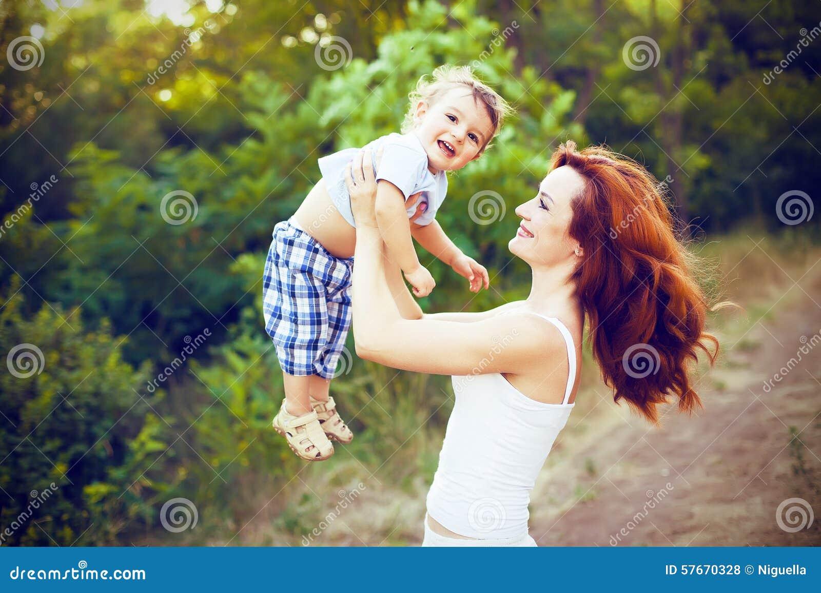 Matka z długim kędzierzawym czerwonym włosy bawić się z jej synem w parku
