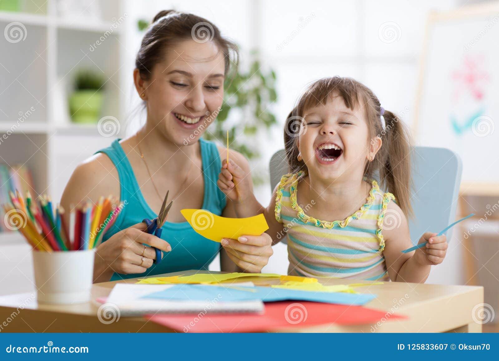 Matka z mali rżnięci nożyce barwiącym córki zabawy papierem