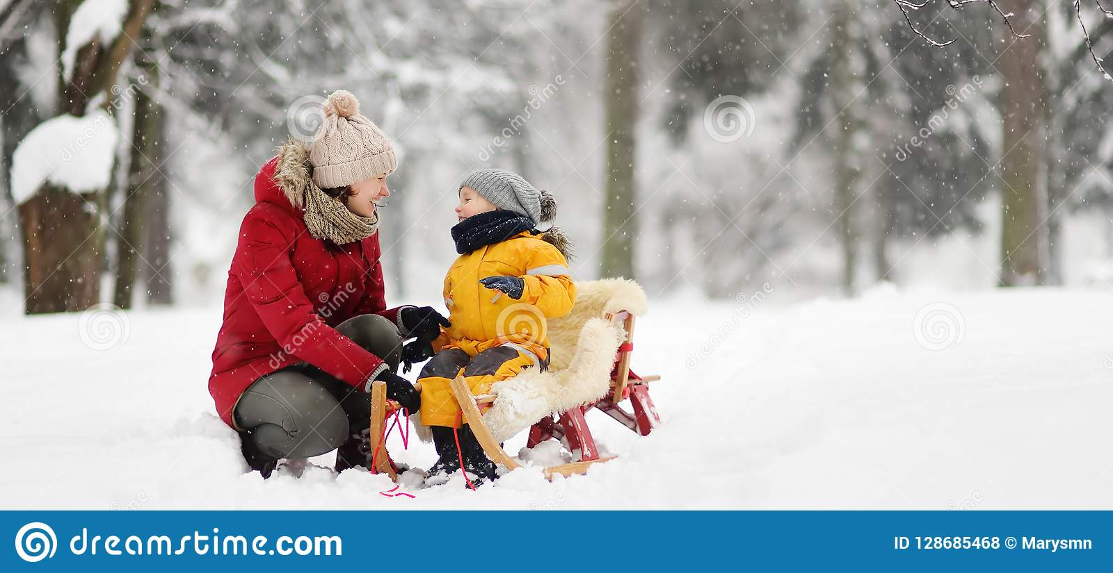Matki, niani rozmowa z małym dzieckiem podczas sledding w zima parku/