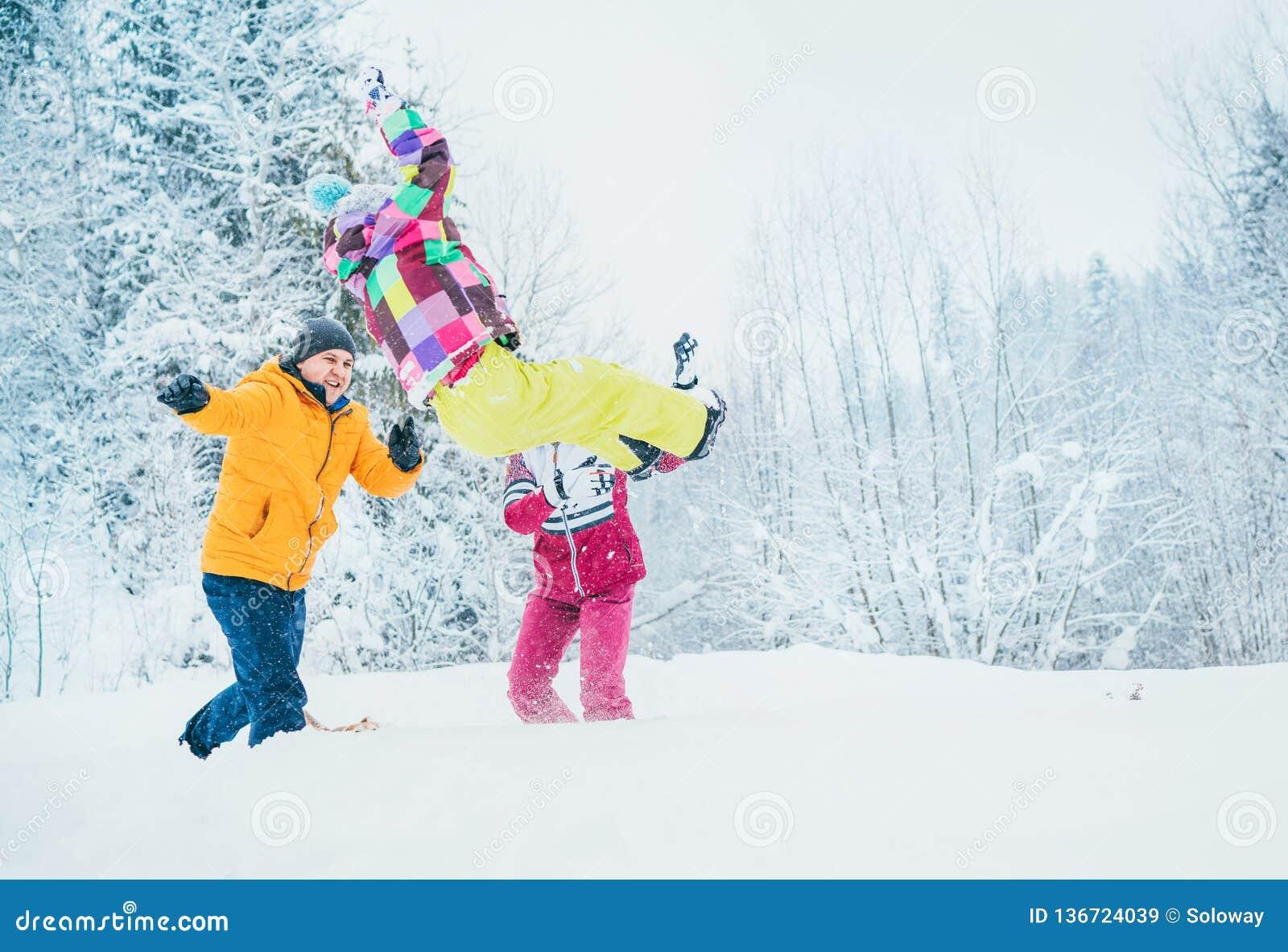 Matkuje rodziny błaź się w śnieżnym lesie rzucać ich małego daugher snowdrift i ojcuje