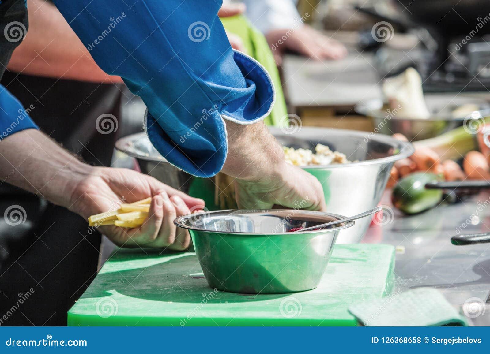 Matlagning Kocken klipper gräsplaner i köket