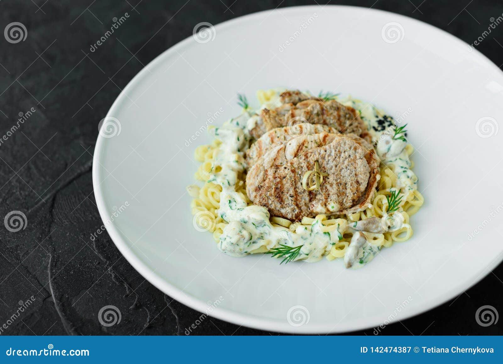 Maträtt med köttstycken, pasta, gräsplaner och sås från gras för en foie