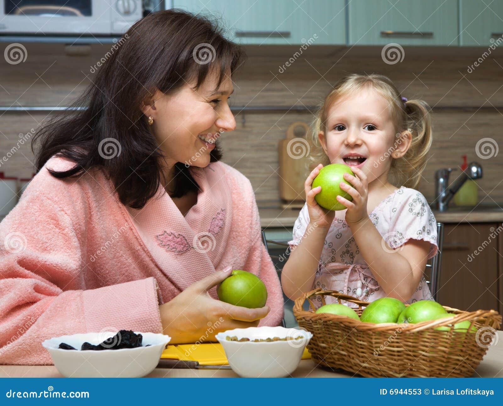A matriz alimenta a criança com maçãs