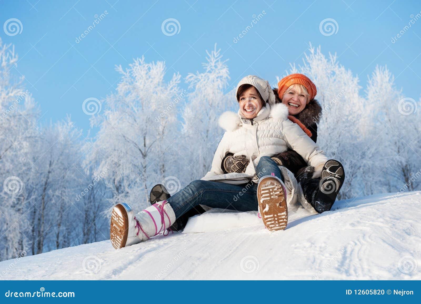 Matriz e filha que deslizam na neve