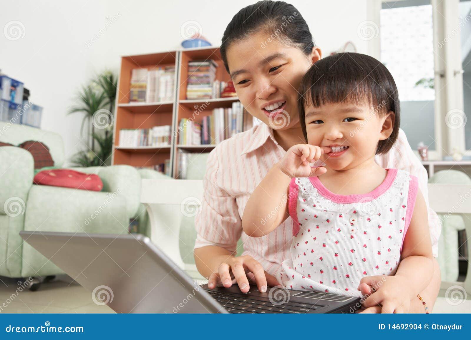Matriz e filha que jogam o portátil junto