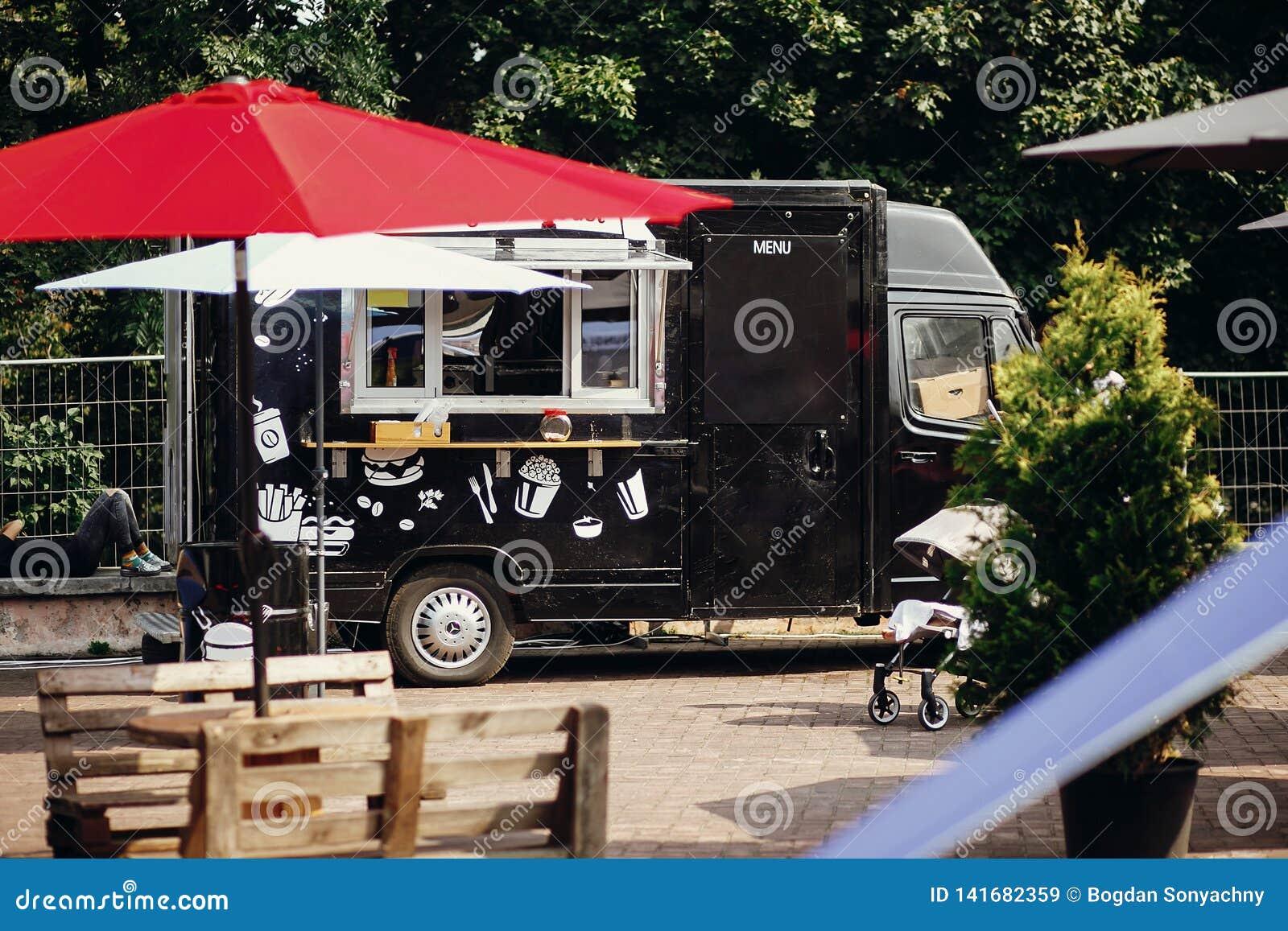 Matskåpbillastbil Stilfull svart mobil matlastbil med hamburgare och asiatisk mat på gatamatfestivalen Sommar som äter marknaden