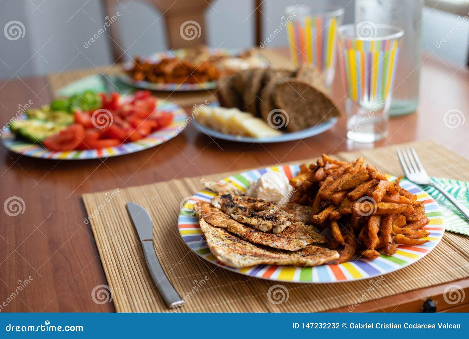 Matställetabell med salladmaträtten, höna, sötpotatisar, bröd och färgrikt vattenexponeringsglas