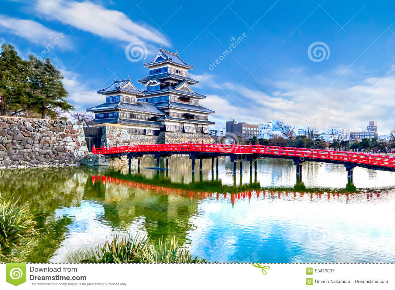 Matsumoto castle against with red wooden bridge over the canal i