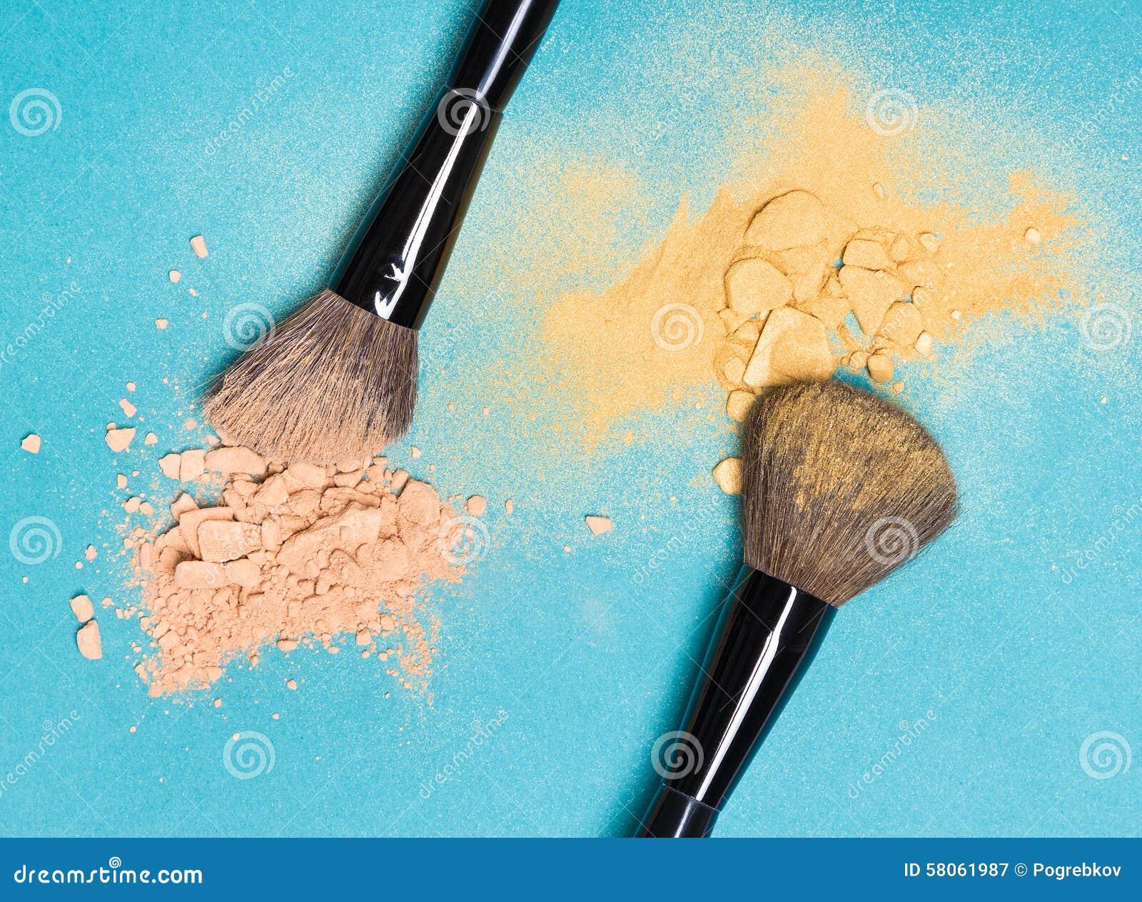 Matteöverenskommelsepulver och skimrar pulver med makeupborstar