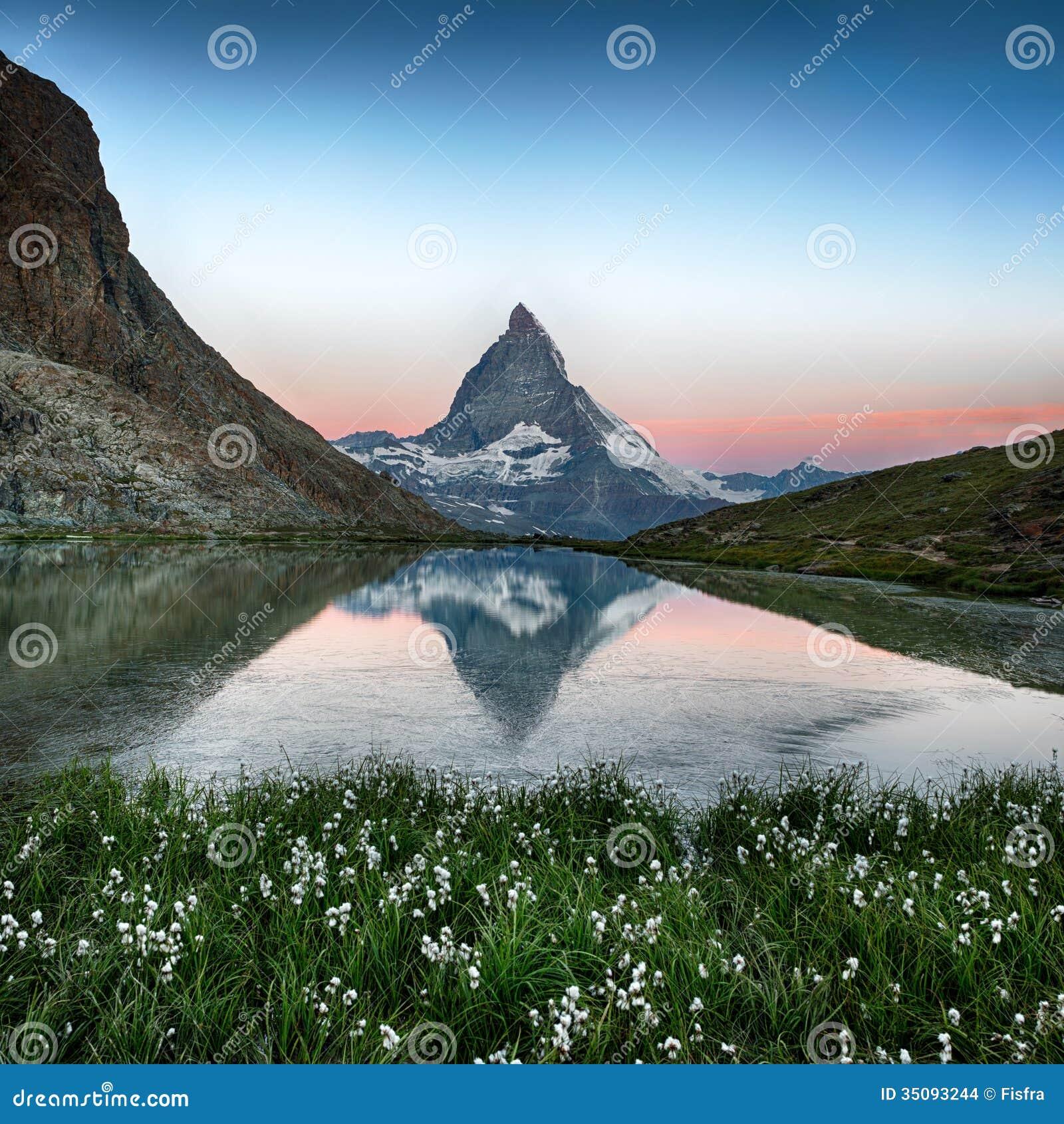 Matterhorn reflection in Riffelsee with flowers, Zermatt, Alps,