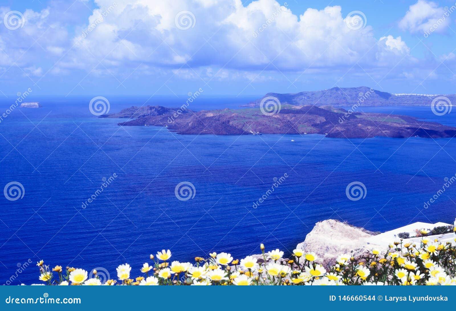 Mattina soleggiata di estate sull isola di Santorini, Grecia Mare blu, cielo blu con le nuvole contro lo sfondo dell isola