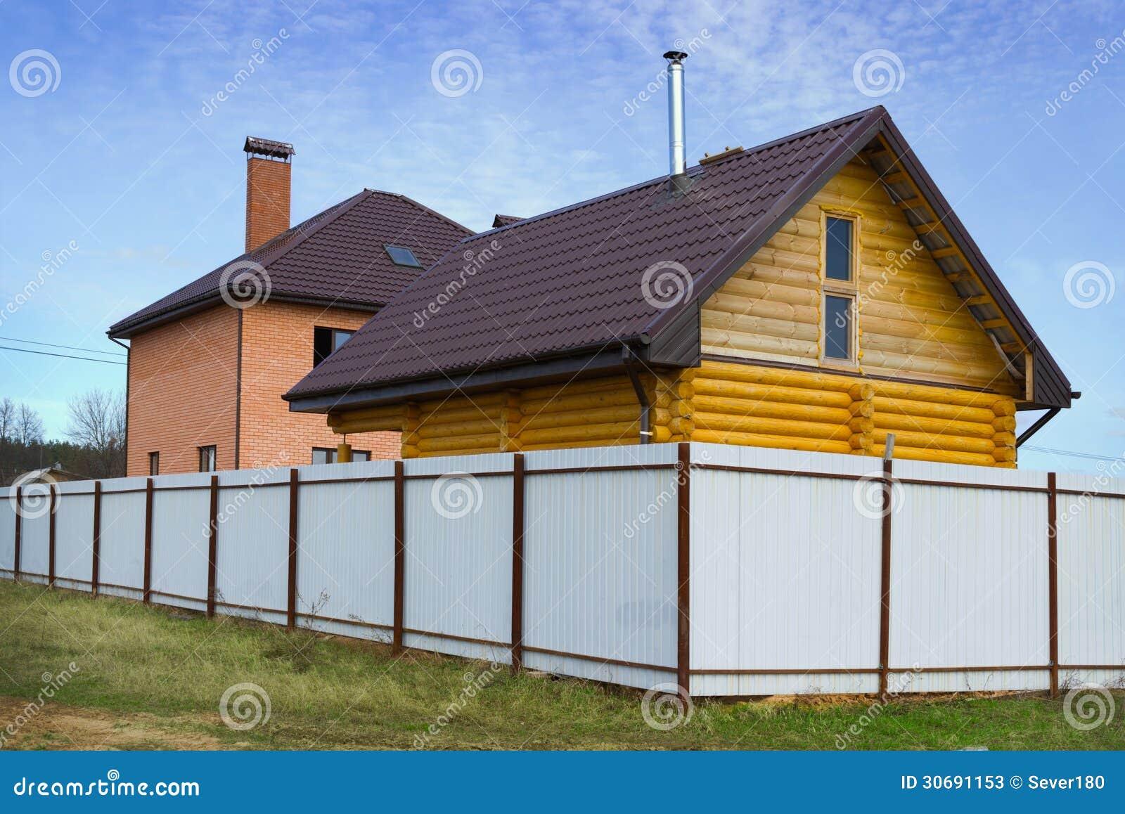 Case Di Legno E Mattoni : Mattone e casa di legno dietro un recinto immagine stock