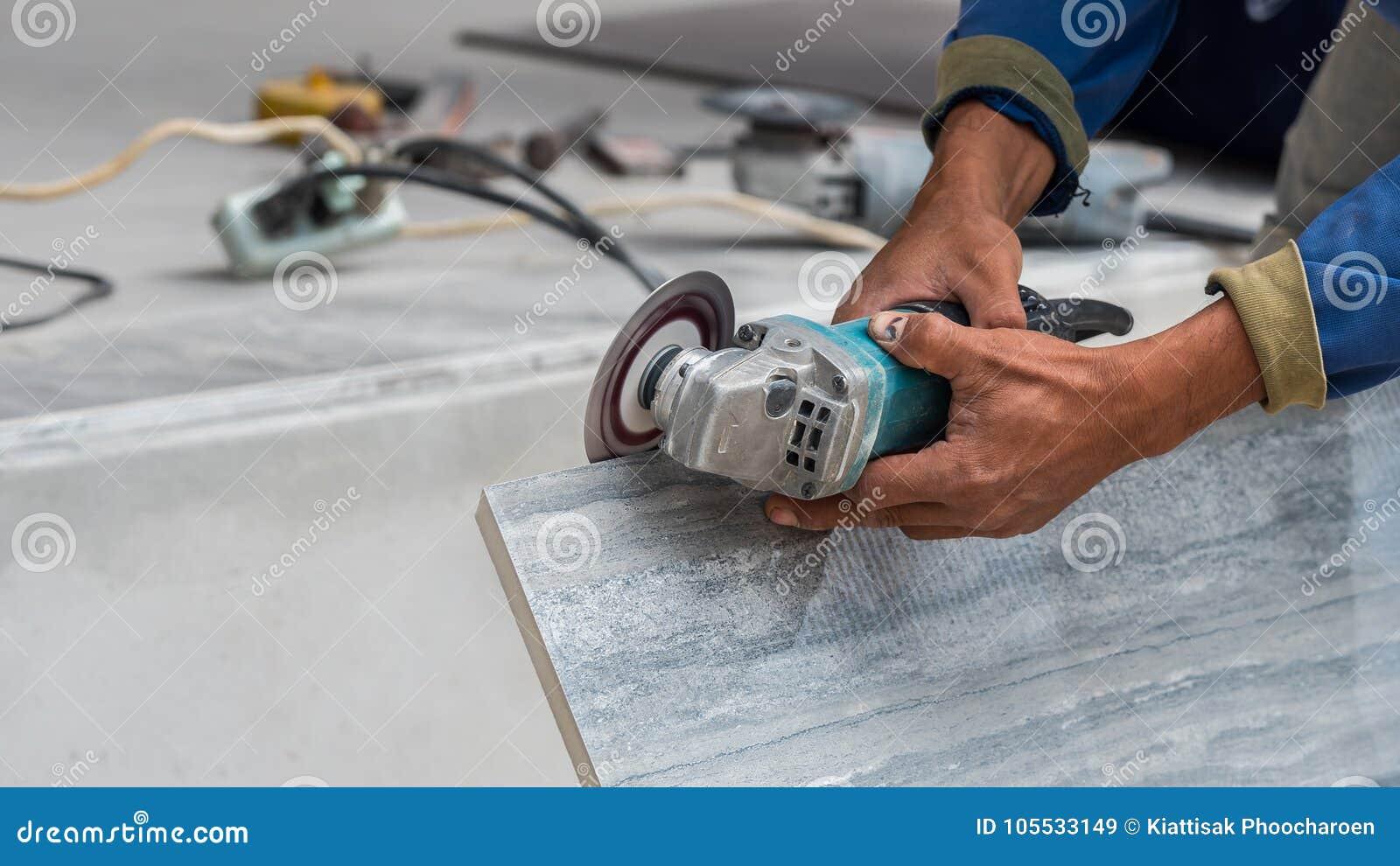 Tagliare piastrelle con smerigliatrice: l operaio taglia piastrelle