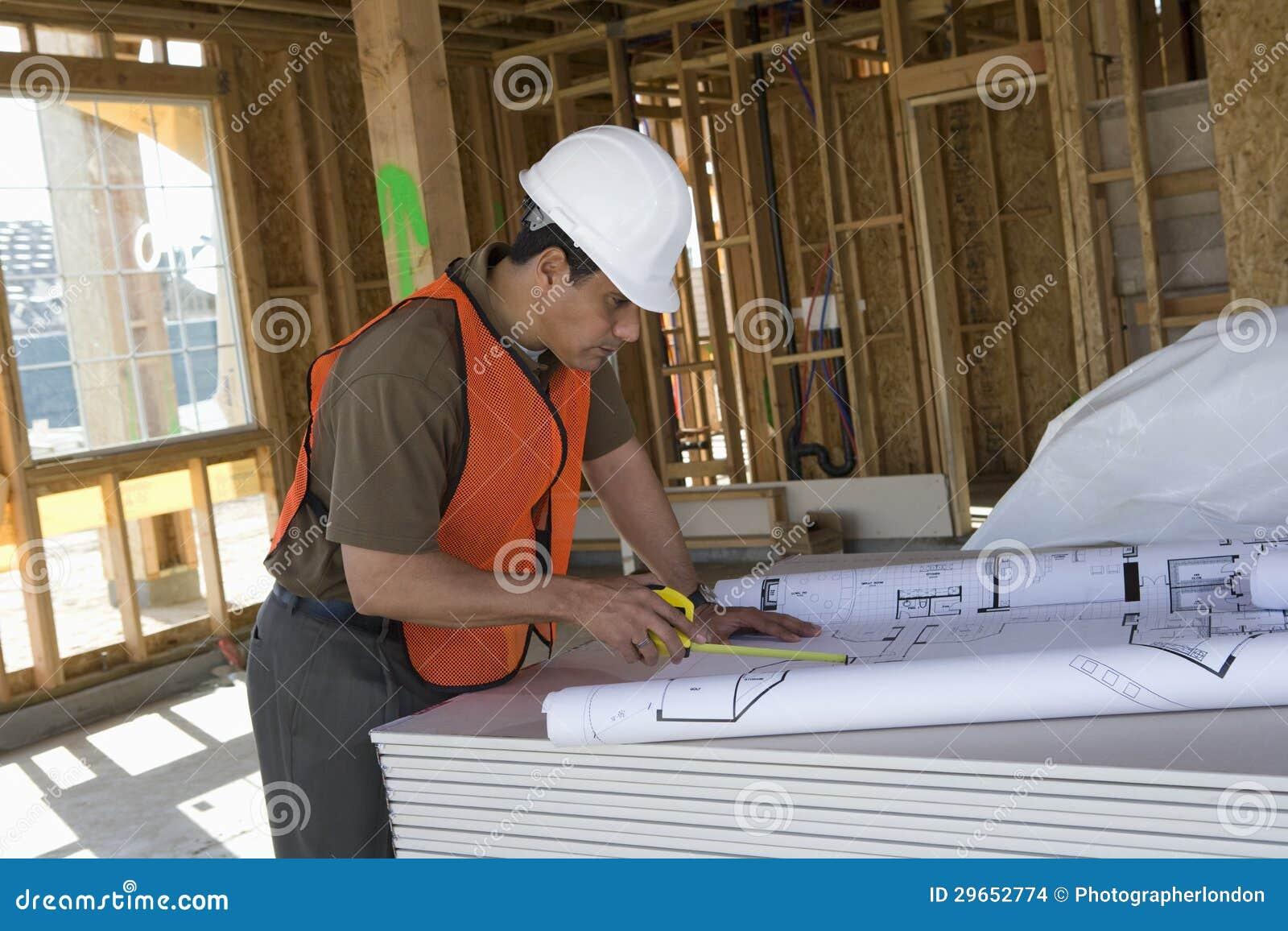 Mature Architect Working On Blueprint