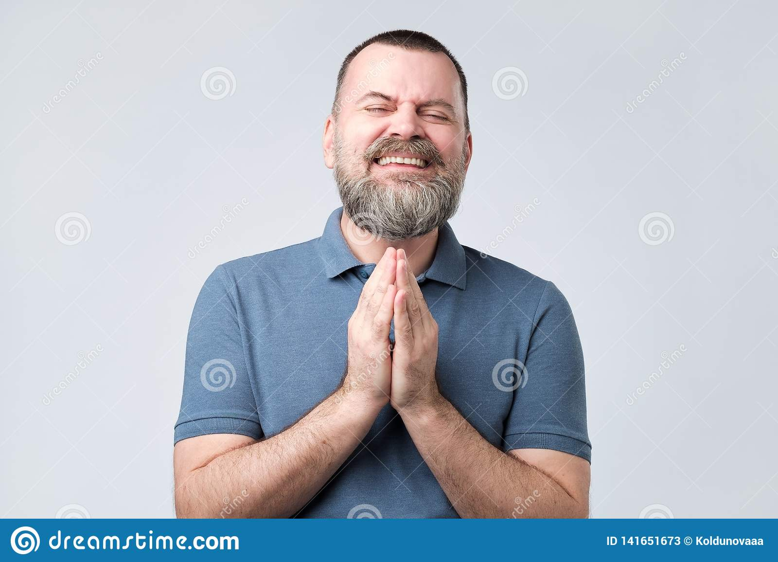 Mature bearded man join hands together begging asking for forgiveness help