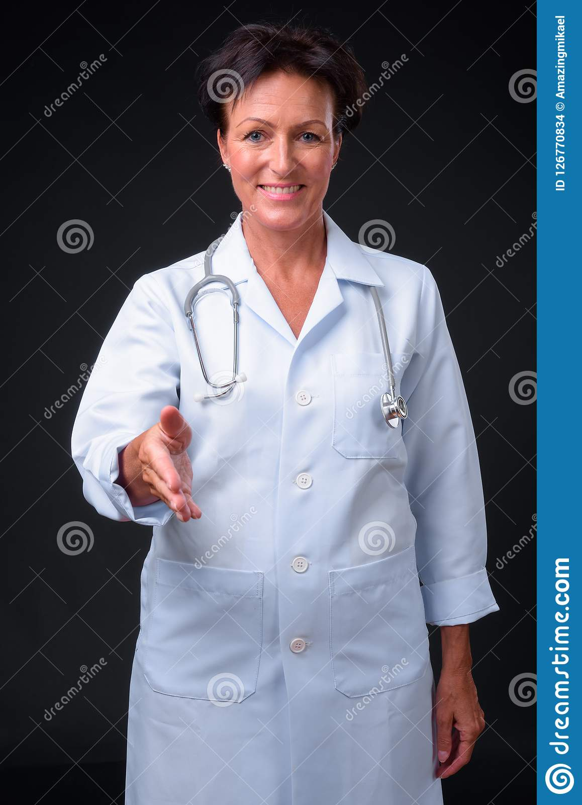 Mature beautiful woman doctor with short hair against black back. Studio shot of mature beautiful Scandinavian woman doctor with short hair against black Stock Images
