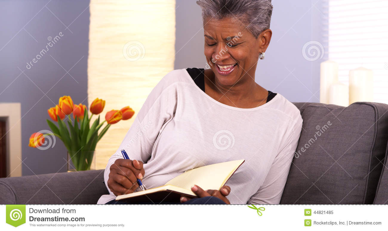 Mature black woman writing in journal