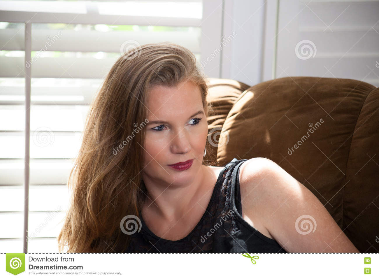 Blonde Female Sitting in front of window looking away from camera.