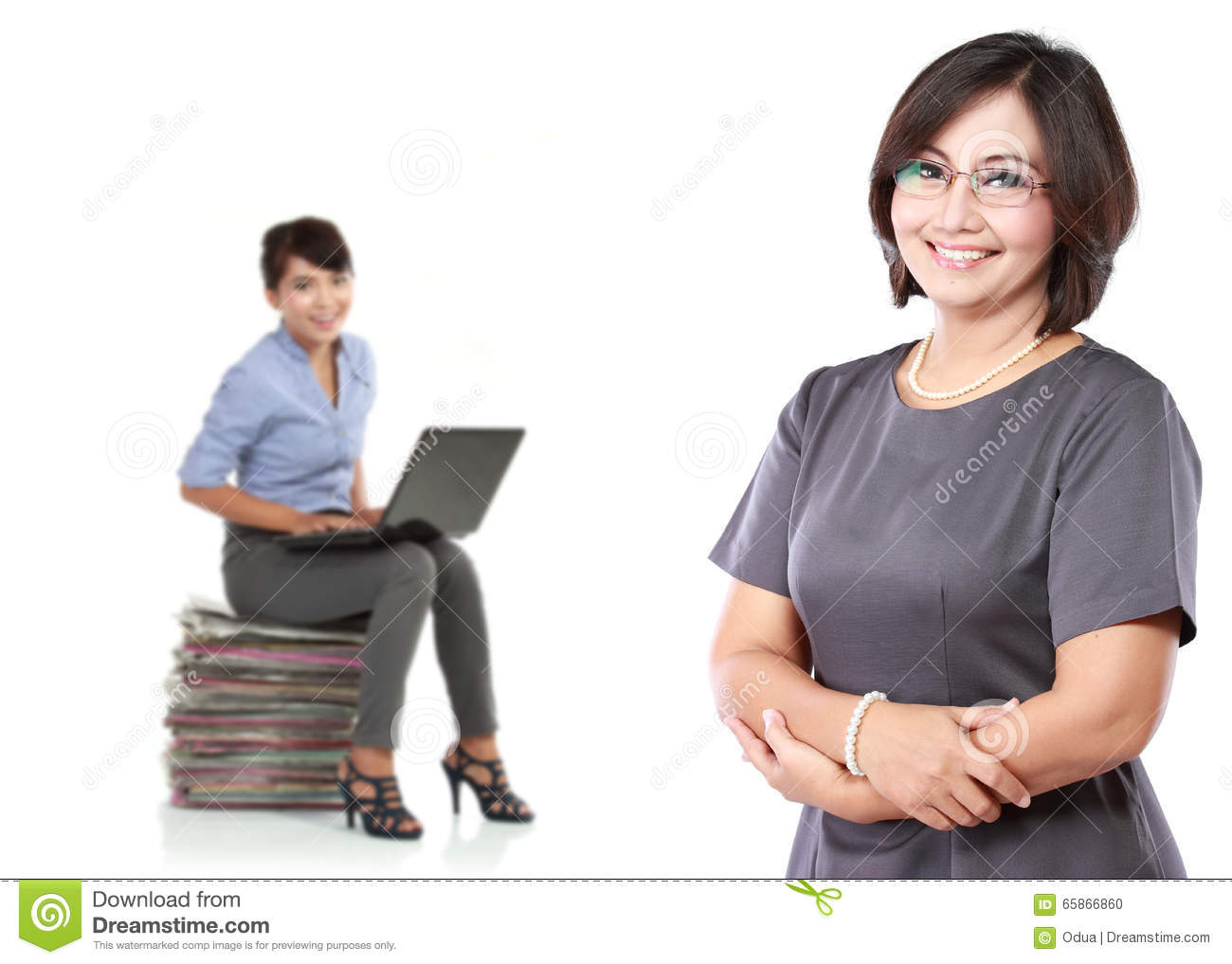 mature business women standing with her secretary behind holding