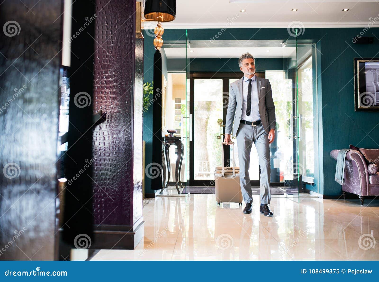 Hotel Entrance Foyer : Mature businessman entering hotel with luggage stock image