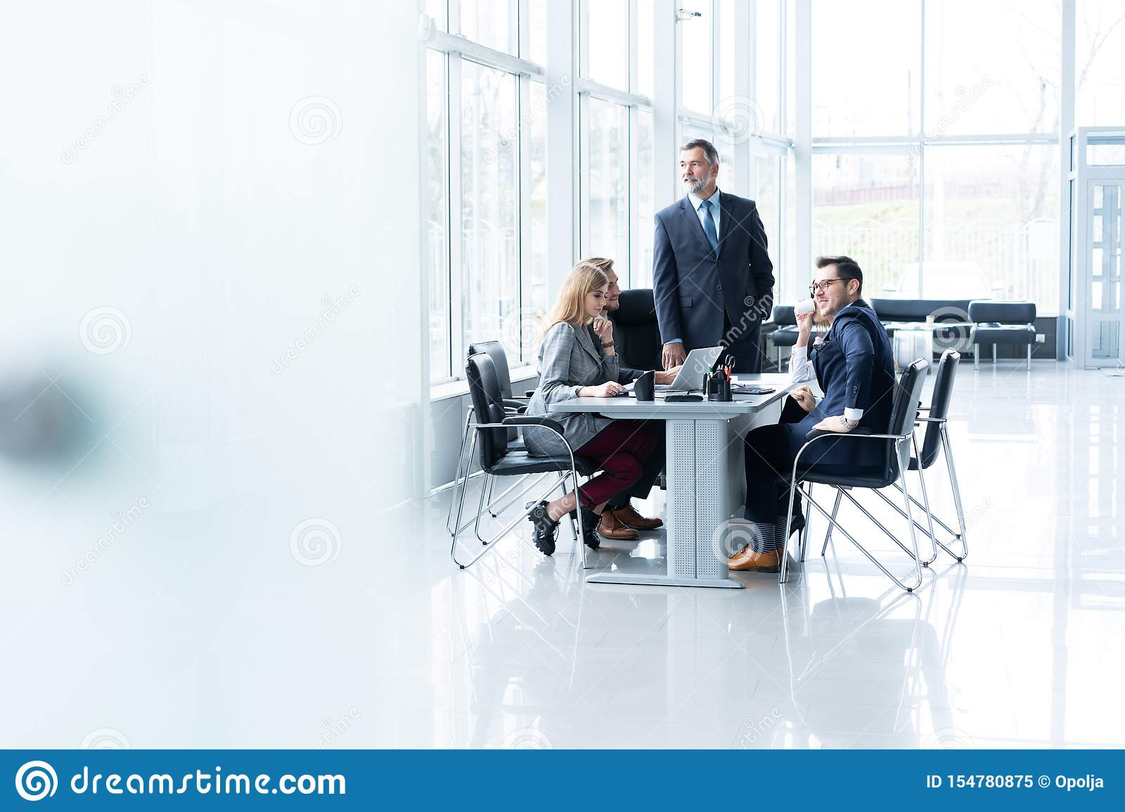 Mature businessman talking and explaining his business strategy to his colleagues at office.