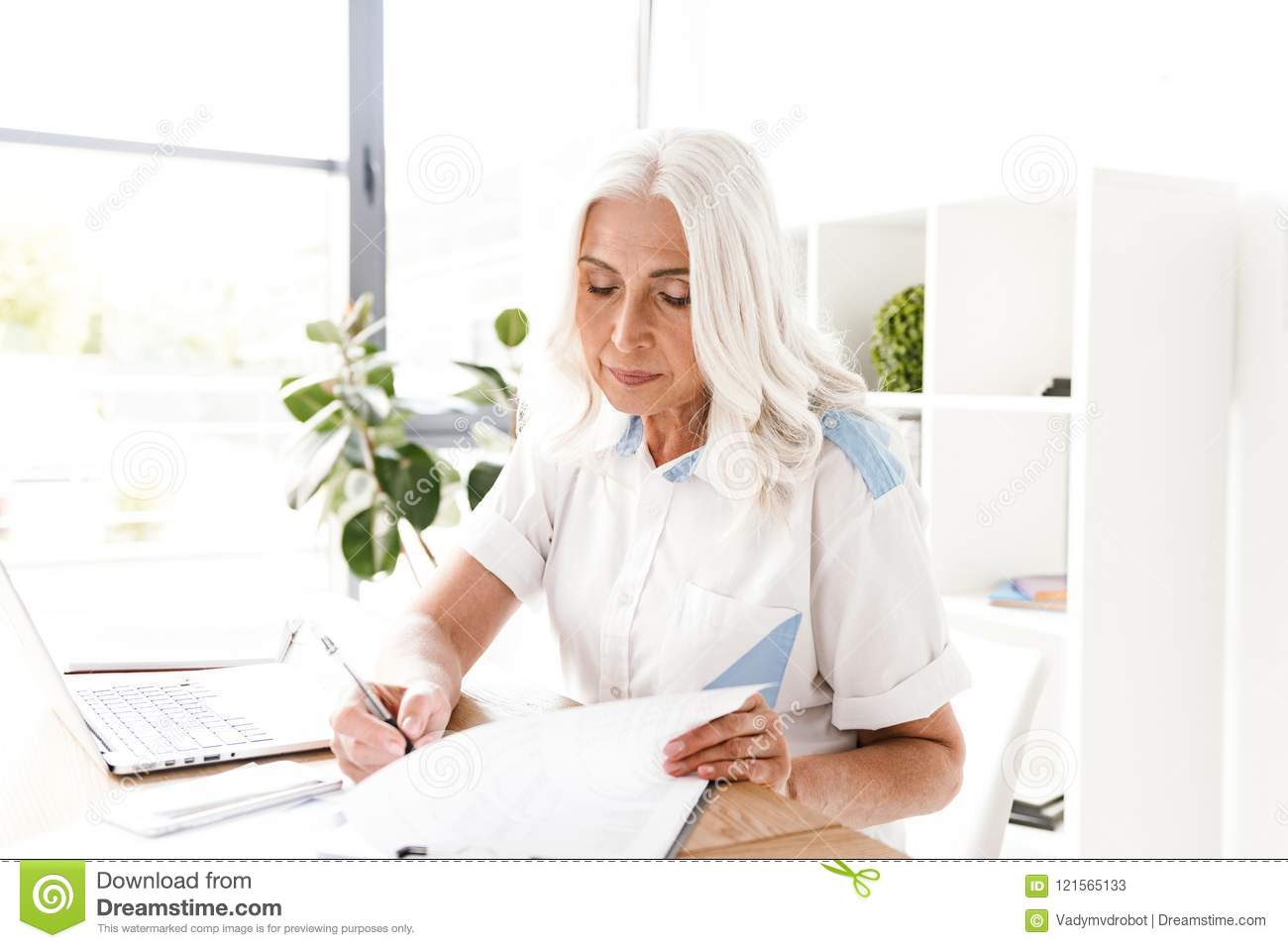 Mature concentrated woman writing notes.