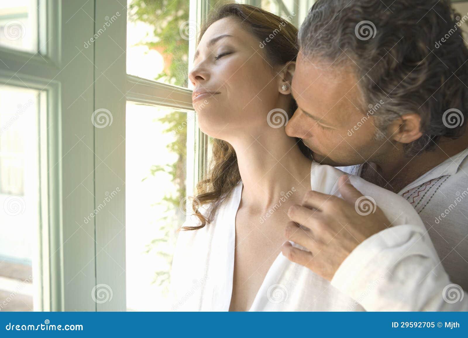 mature couple kissinggarden doors. stock image - image of doors