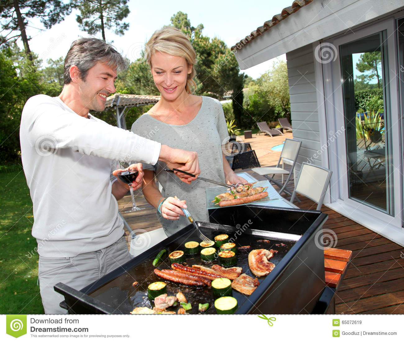 Mature Couple Making Barbecue Dinner On Terrace Stock Image - Image ...