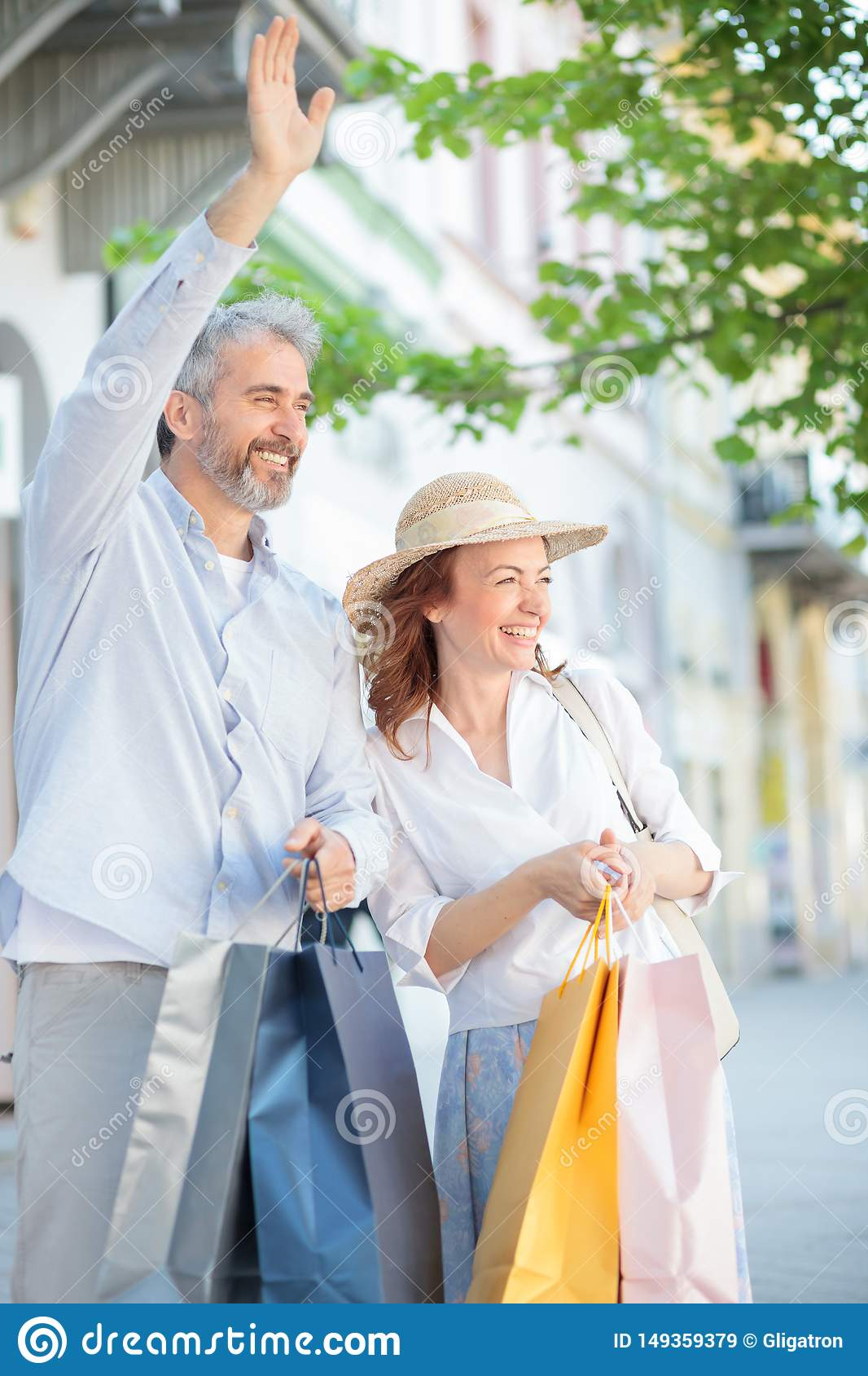Mature couple returning from shopping, carrying full shopping bags and waving to friends