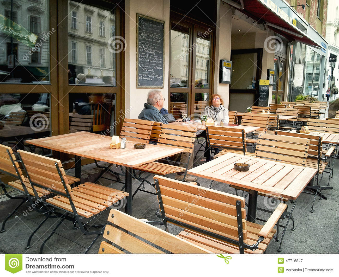Mature Couple Sitting In An Empty Street Cafe Editorial