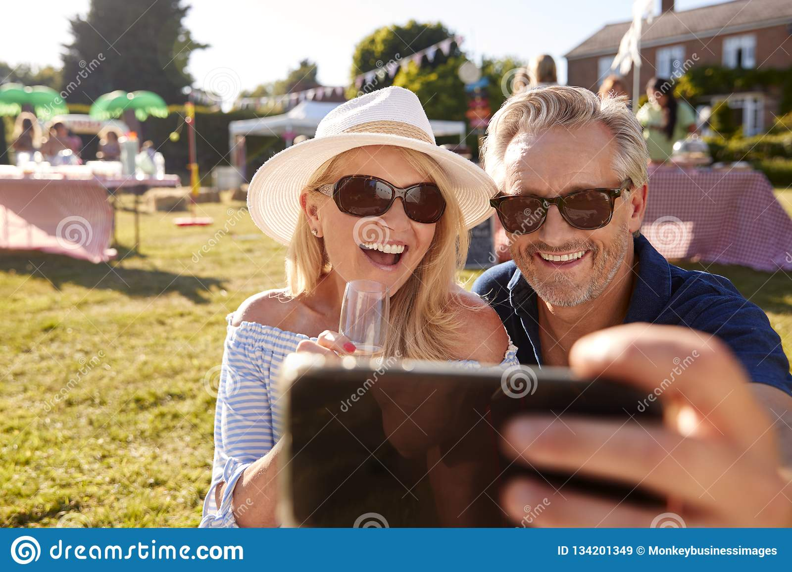 Mature Couple Sitting On Rug At Summer Garden Fete Taking Selfie On Mobile Phone
