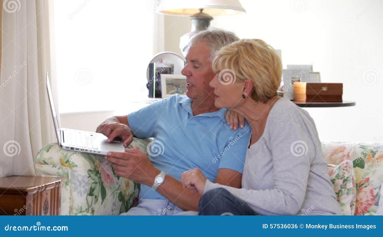 Mature Couple Sitting On Sofa Using Laptop Stock Footage - Video of  lockdown, laptop: 57536036