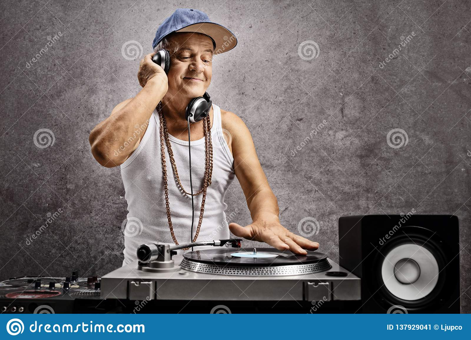 Mature dj with headphones playing music at a turntable