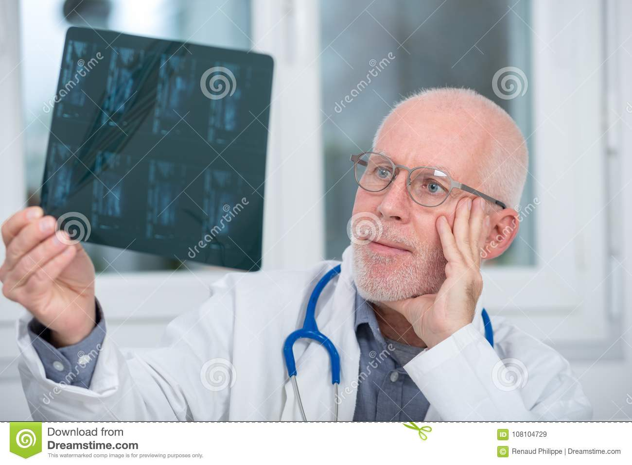 Mature Doctor looking at an x-ray in an office