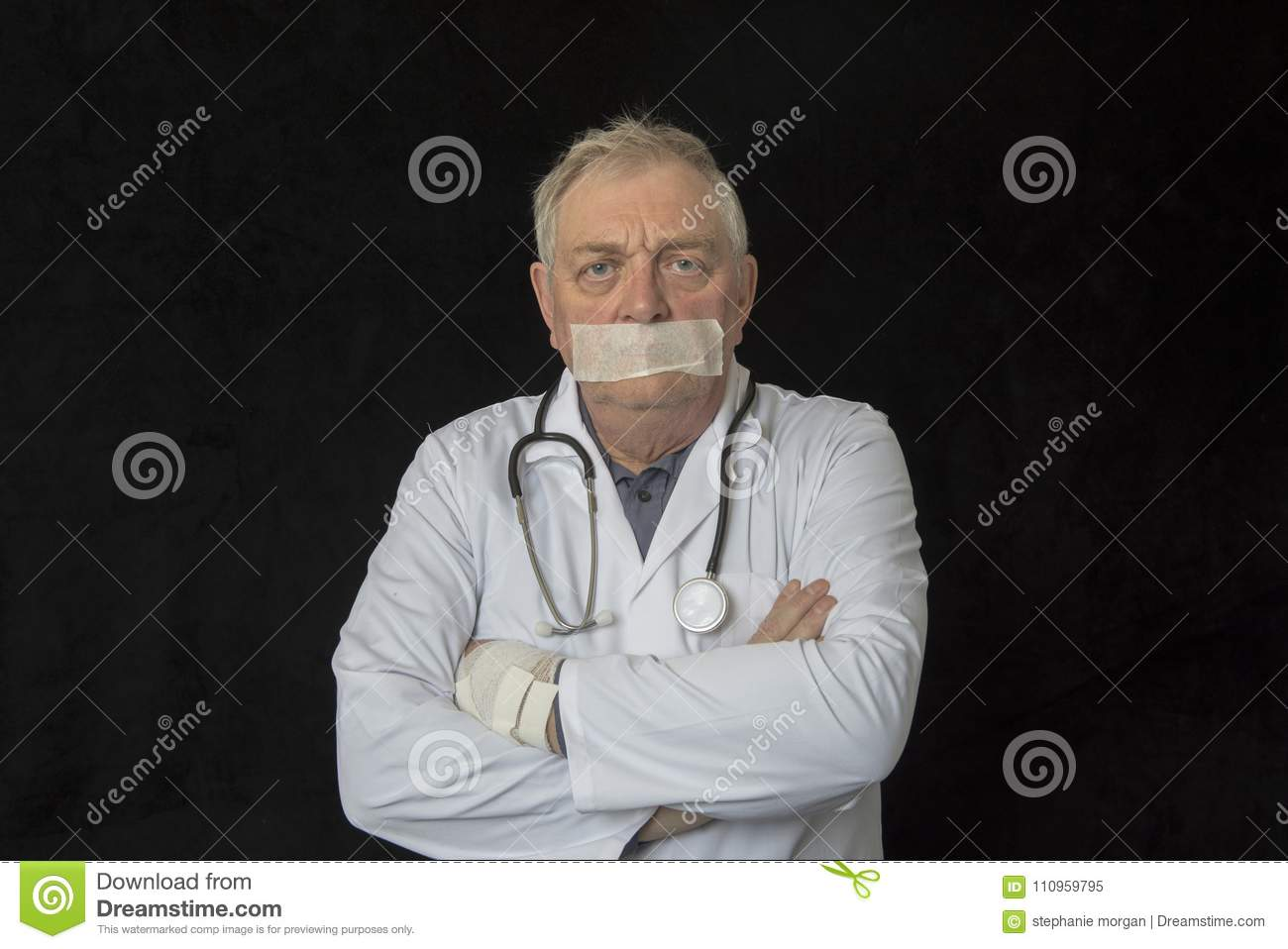 Mature doctor with tape across his mouth
