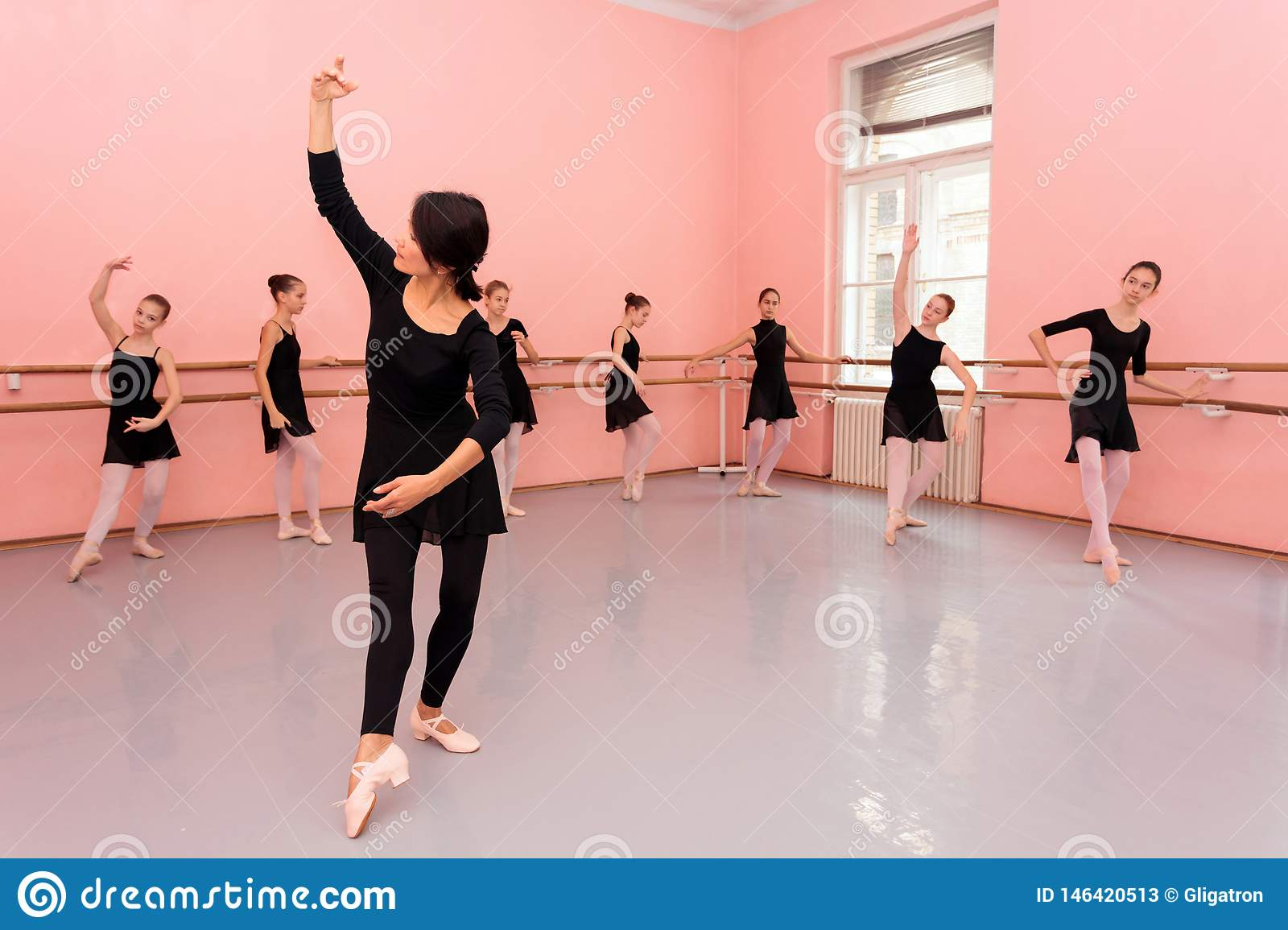 Mature female ballet teacher demonstrating dancing moves in front of a group of young teenage girls