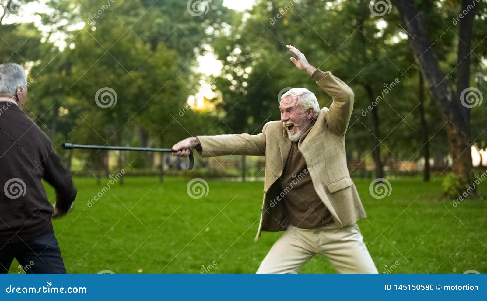 Mature friends having fun, fighting with walking sticks, pretending be knights