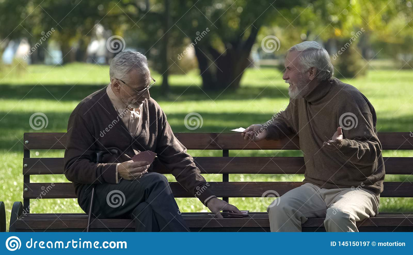 Mature friends playing cards having fun in park, active lifestyle, retirement