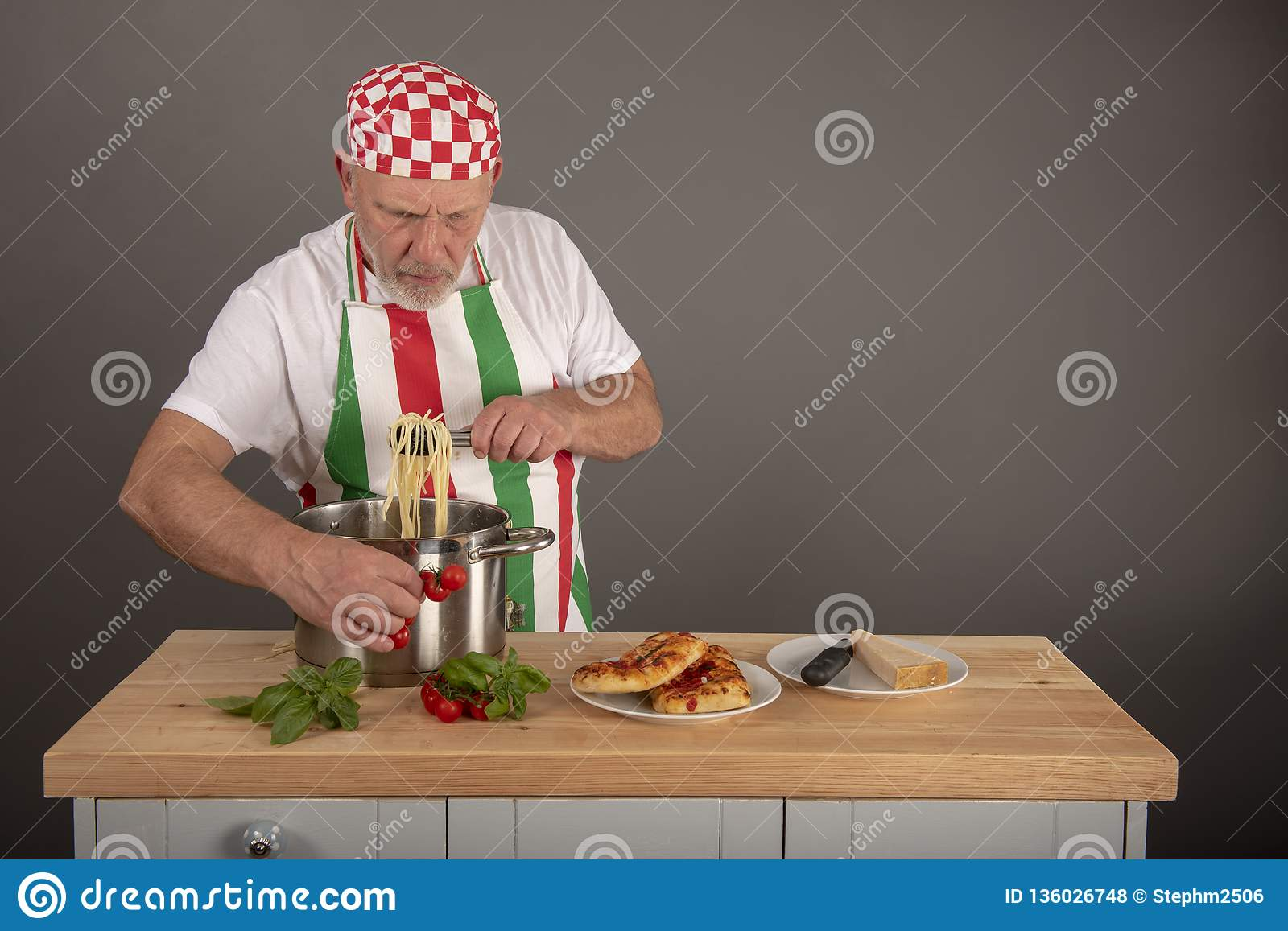 Mature Italian Chef plating up a pasta dish