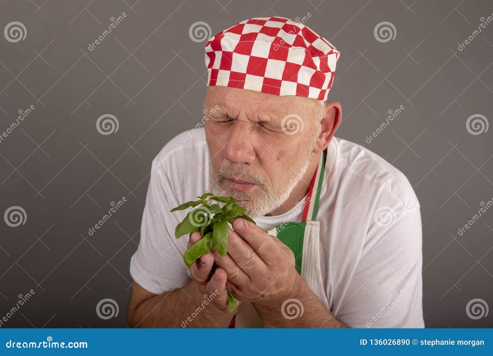 Mature Italian chef smelling basil leaves