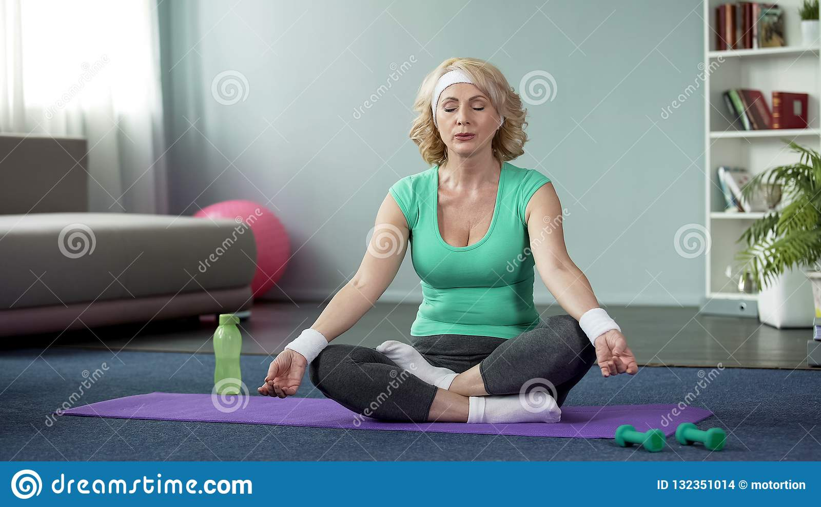Mature lady practicing yoga at home, doing relaxation exercises, meditation