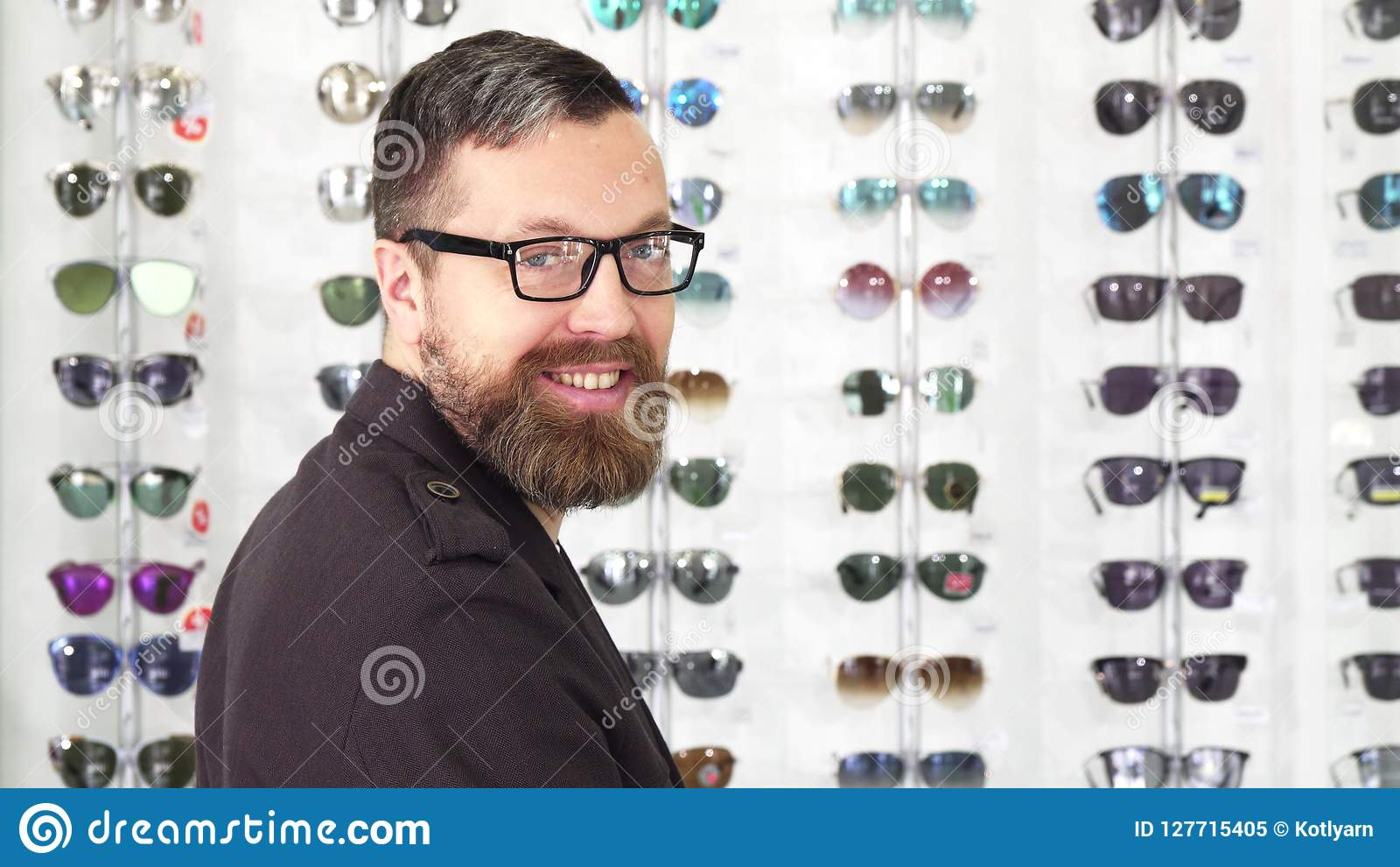ef98211b72e6 Rear view shot of a bearded mature man examining sunglasses for sale on the  display at the opticians store smiling to the camera over his shoulder ...